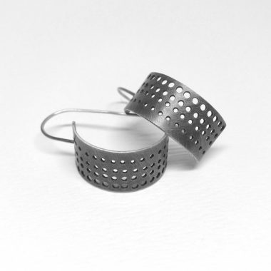 Sterling silver hoop earrings with a gradation of drilled holes. Jane Pellicciotto.