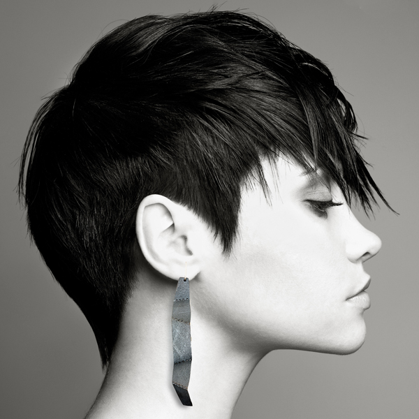 Model wearing perforated, folded sterling silver earrings by Jane Pellicciotto