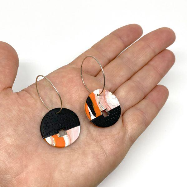 Orange swirl and black disc polymer clay earrings. Jane Pellicciotto
