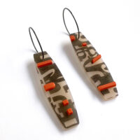 Type collage earrings with orange accents. Polymer clay and sterling silver. Jane Pellicciotto